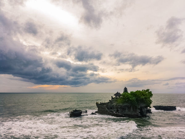 Tanah Lot Temple in Bali, Indonesia. This place stays isolated by ocean water until the end of the day when the water level goes down. Only then people can visit it. Introvert EyeEmNewHere Indian Ocean Temple Hindu Remote Island Bali INDONESIA Ocean Travel Beautiful Unique Sea Cloud - Sky Beach Horizon Over Water Outdoors Sky Built Structure Water No People Day Architecture Beauty In Nature Tree Sunset Travel Destinations Nature