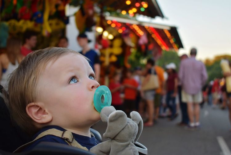 Cute Baby Boy Holding Pacifier While Sitting In Carriage At Market