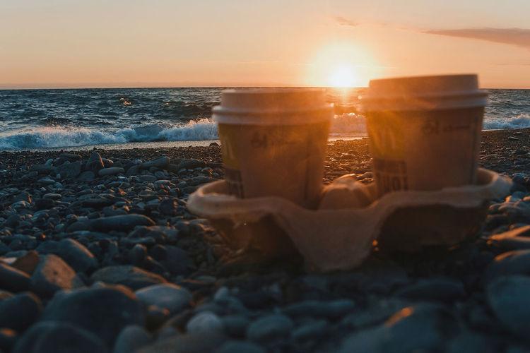 Water splashing on rocks at beach against sky during sunset