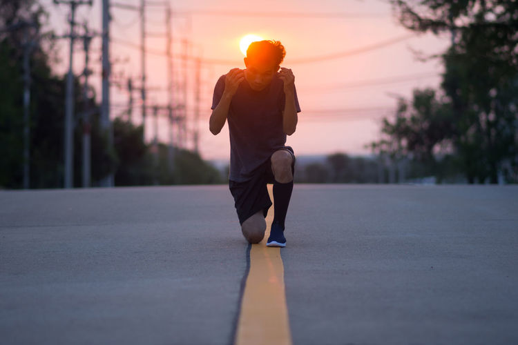 Man running on road at sunset