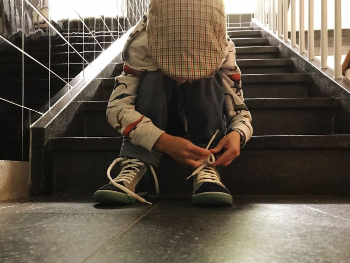 EyeEm Selects Child Tying Shoelaces Tying Shoelace Learning Real People One Person Lifestyles Indoors  Steps And Staircases Sitting Full Length Boys Childhood Low Section Day People