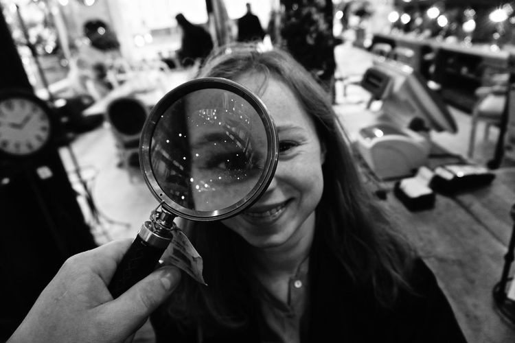 Happy woman seen through magnifying glass in shop