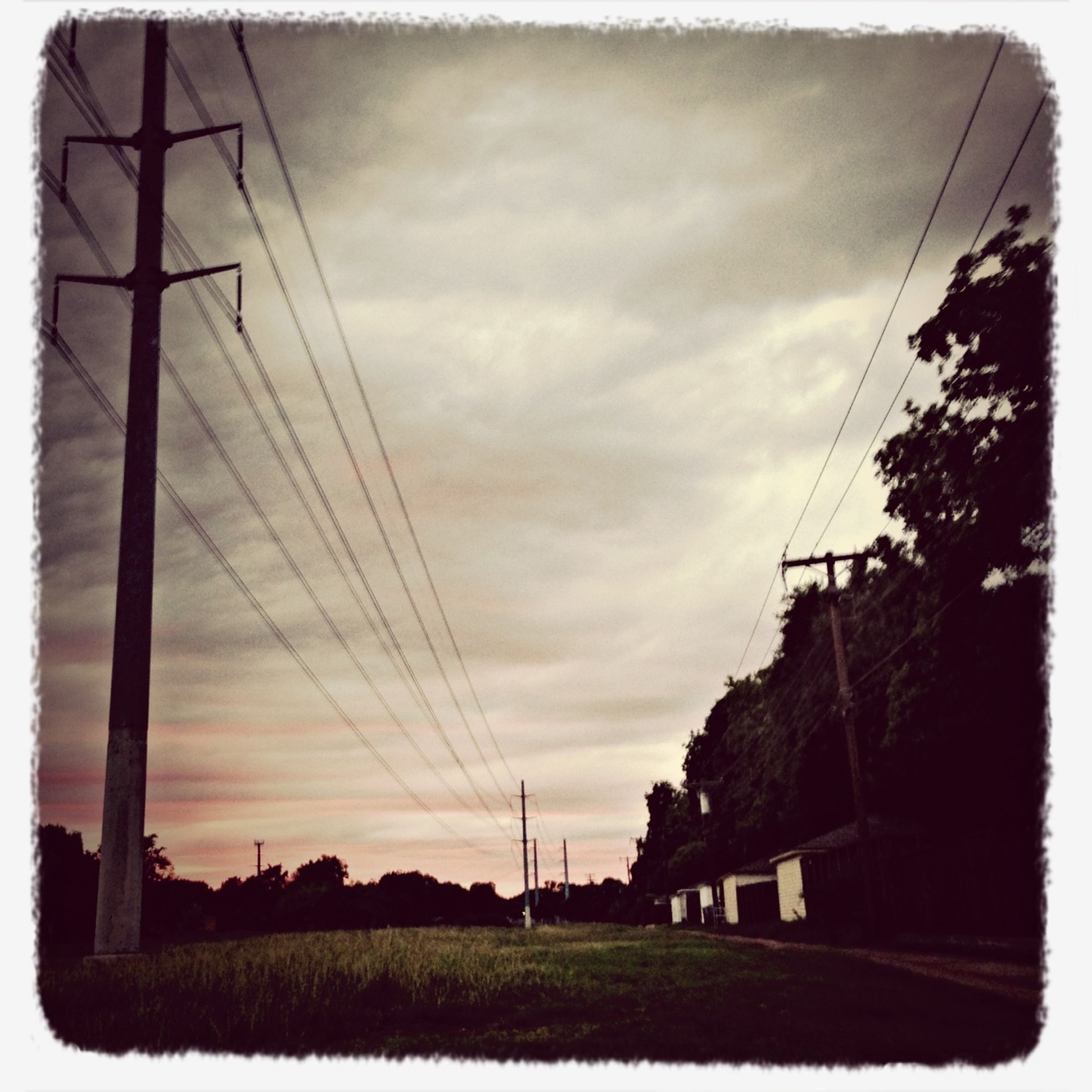 power line, electricity pylon, power supply, sky, transfer print, electricity, cable, connection, built structure, architecture, building exterior, auto post production filter, cloud - sky, fuel and power generation, power cable, sunset, house, cloud, low angle view, cloudy