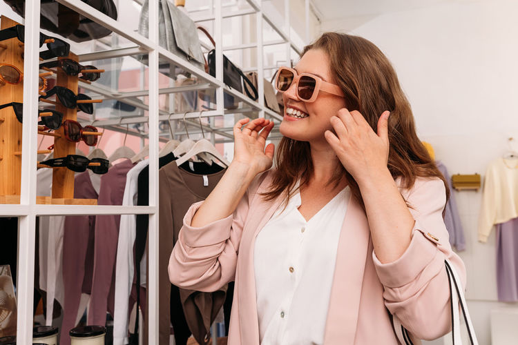 Young woman smiling while standing in store