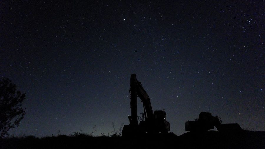 Low angle view of heavy machinery against sky at night