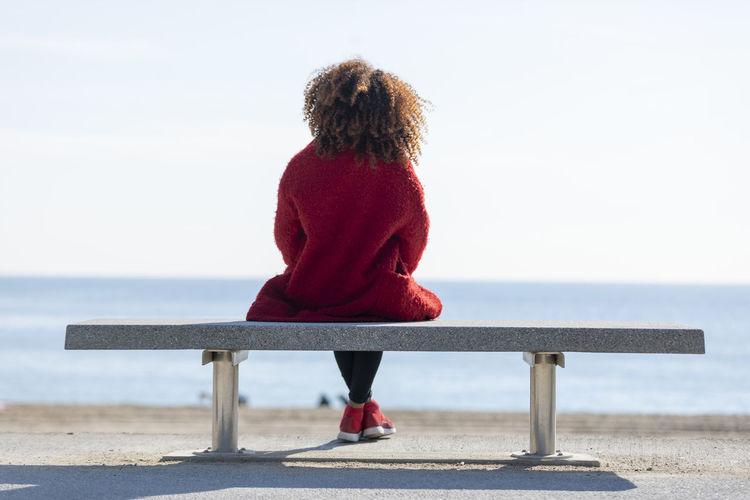 Rear view of a young curly woman wearing red denim jacket sitting on a bench while looking away to horizon over sea One Person Leisure Activity Rear View Real People Sea Women Water Lifestyles Full Length Seat Sky Sitting Bench Day Nature Beauty In Nature Horizon Over Water Horizon Red Hairstyle Outdoors Hair Looking At View Horizontal African American Red Jacket Happiness Beautiful Enjoying Life Attractive Standing Looking At Camera Looking Away Young Adult Curly Hair Outside Stylish Fashion Model Lady Sunny Daylight