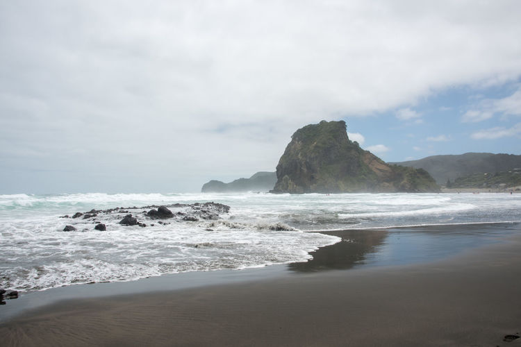 Famous Piha Beach with volcanic black sand in Auckland, New Zealand Auckland Flowing Lion Rock Tasman Sea Beach Black Cloud - Sky Famous Place Geology Horizon Over Water Motion Nature New Zealand Physical Geography Piha Power In Nature Rock Sand Scenics - Nature Sea Stack Rock Tranquility Volcanic Landscape Volcano Water