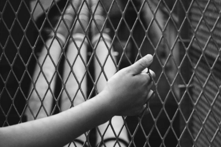 Close-Up Of Hand On Chainlink Fence