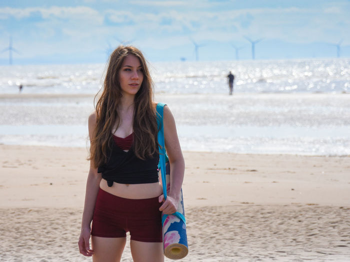 Beautiful Young Woman Standing With Exercise Mat On Beach