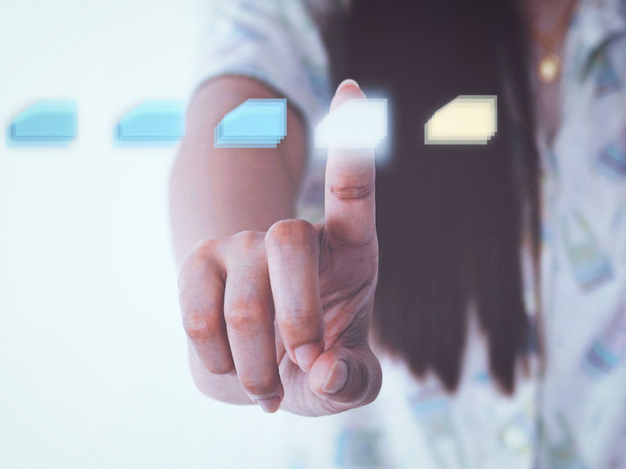 Digital composite image of woman touching button on invisible screen with icon