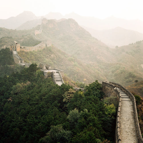 China's Great Wall winds its way into the distance on a hazy morning. Architecture Beauty In Nature Built Structure China Day Film Great Wall Of China Hazy  High Angle View Landscape Morning Morning Light Mountain Mountain Range Nature No People Outdoors Scenics Sky Sunrise Tranquility Travel Destinations Travel Photography Tree Winding Road