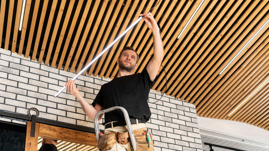 An electrician installs low voltage led lamps in a plank ceiling. builder assembles loft ceiling.