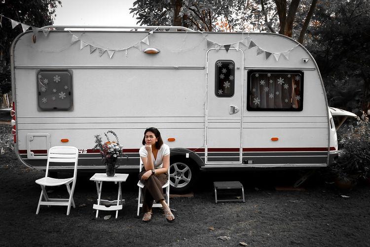 Full length portrait of woman sitting against bus