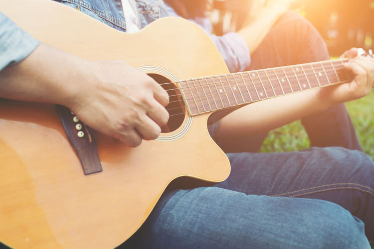 Midsection of man playing guitar by friend at park