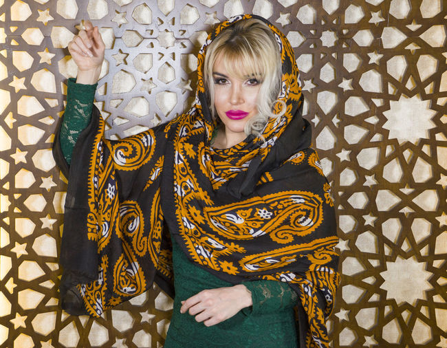 Portrait of woman wearing scarf standing against wall