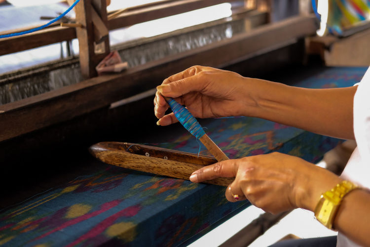 Midsection of worker preparing needle at handloom factory