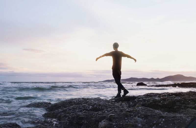 male arms outstretched on the beach with nice sunset Arms Outstretched Arms Raised Beach Beauty In Nature Horizon Over Water Human Arm Lifestyles One Person Outdoors Real People Rear View Scenics - Nature Sea Sky Sunset Wave