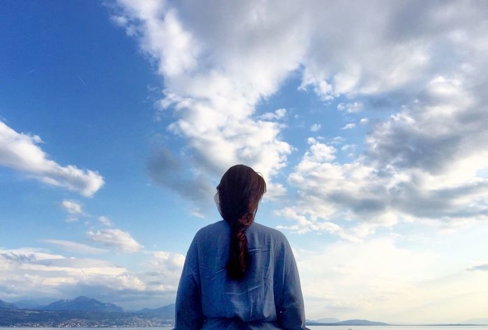 Cloud - Sky Sky One Person Lifestyles Leisure Activity Real People Beauty In Nature Rear View Standing Tranquil Scene Blue Casual Clothing Outdoors Hairstyle