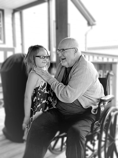 Cheerful grandfather with granddaughter sitting on wheelchair