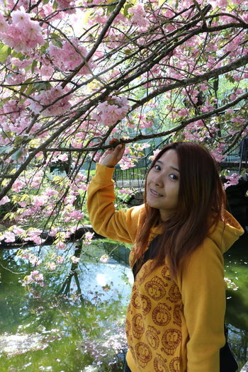 Real People Plant Tree One Person Flower Young Women Standing Lifestyles Flowering Plant Leisure Activity Waist Up Young Adult Portrait Fragility Freshness Beauty In Nature Nature Springtime Women Casual Clothing Hair Hairstyle Pink Color Outdoors Beautiful Woman Human Arm