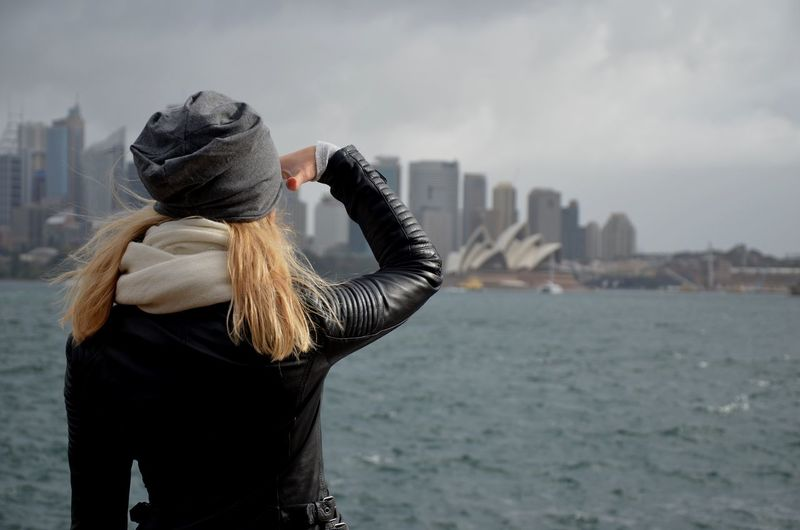 Rear View Of Woman Shielding Eyes While Looking At Sydney Opera House