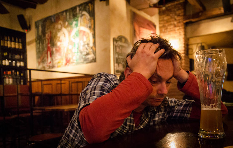 Drunk man sitting at table in bar