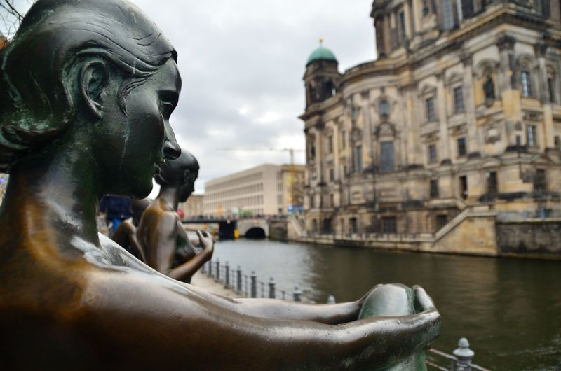 Woman's statue looks at the berlin cathedral