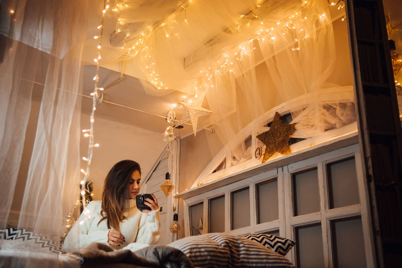 Indoors  One Person Women Young Adult Leisure Activity Real People Furniture Lifestyles Adult Young Women Sitting Illuminated Holding Long Hair Lighting Equipment Curtain Domestic Room Hairstyle Bed Ceiling 2018 In One Photograph