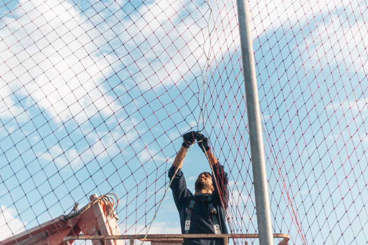 Low angle view of people on chainlink fence against sky