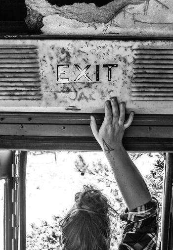 Cropped hand of woman touching exit sign in bus