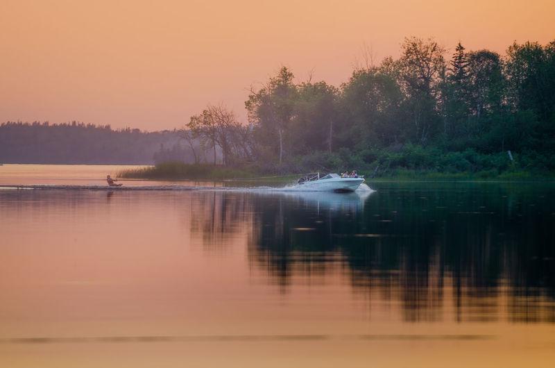 Woman wakeboarding on lake during sunset