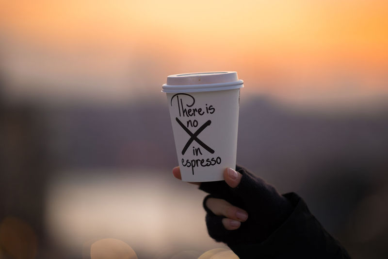 Cropped Image Of Person Holding Disposable Coffee Cup With Text During Sunset