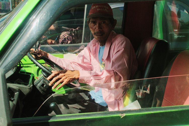 Driver of local transportation called angkot in Bogor, Indonesia. December 2017 Streetphotography Documentaryphotography Transportation Local Transport City Transportation Car Working Drive Driver Driving Green Red Contrast UNPOSED Candid One Person Real People Lifestyles Day Men People One Man Only Adult EyeEm Ready