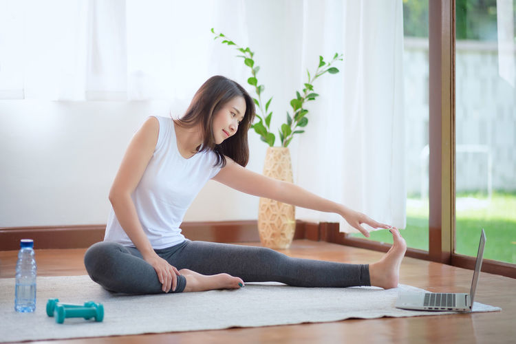 Full length of woman stretching while sitting at home