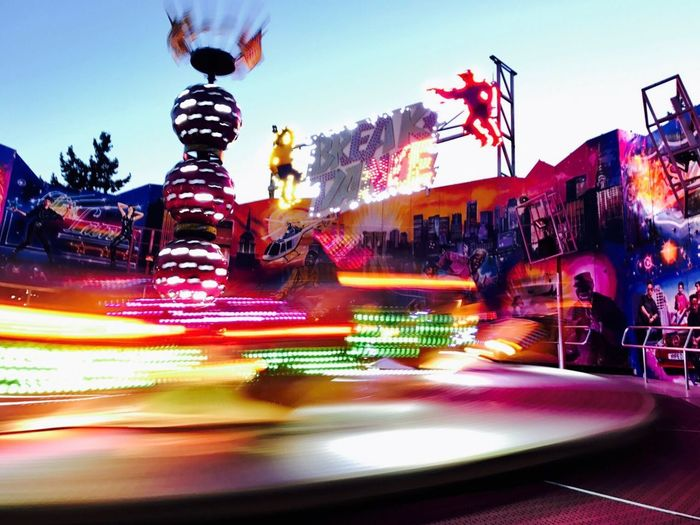 Light trails in amusement park against sky at night