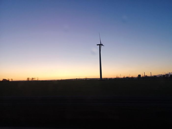 Silhouette of wind turbines on landscape against sky during sunset