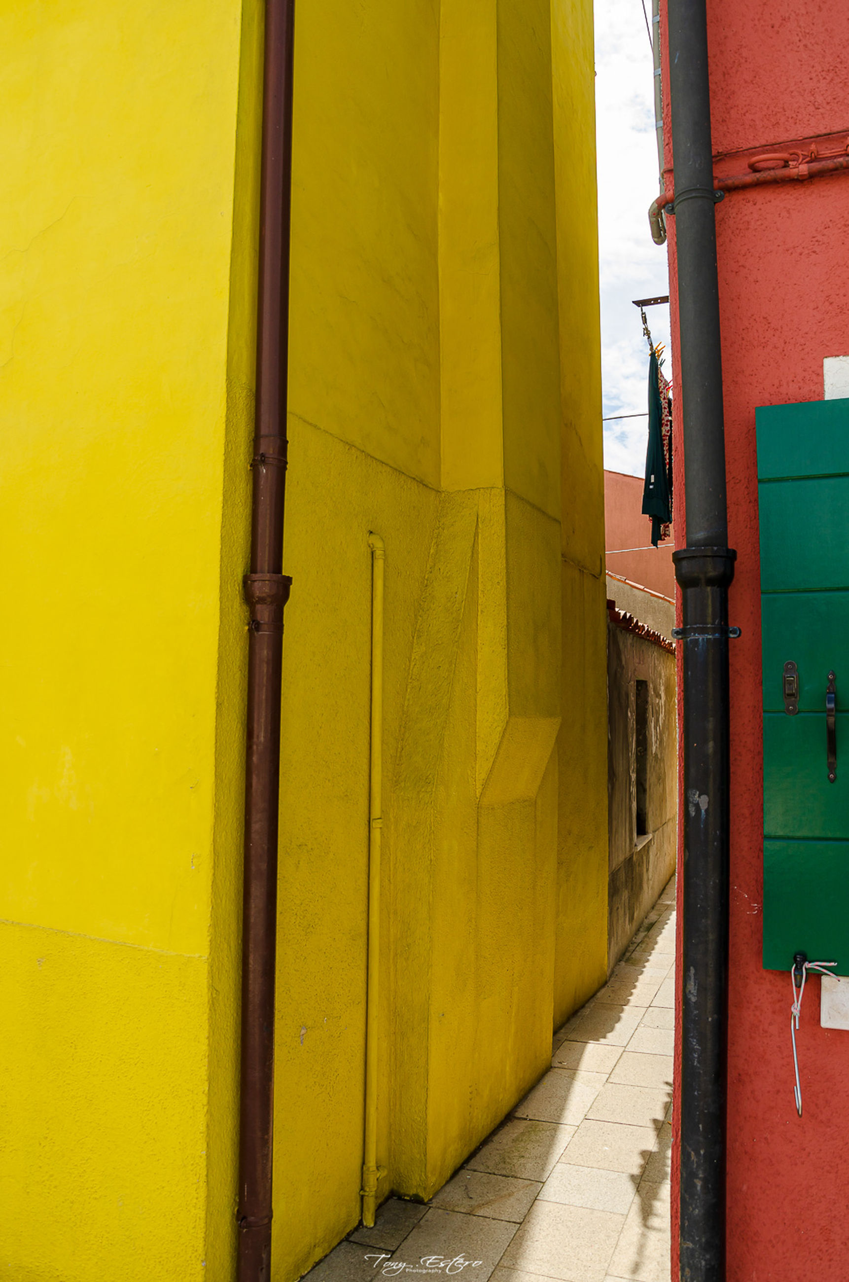 yellow, architecture, built structure, building exterior, building, entrance, door, day, no people, outdoors, wall - building feature, footpath, residential district, direction, closed, sunlight, city, nature, the way forward, pipe - tube