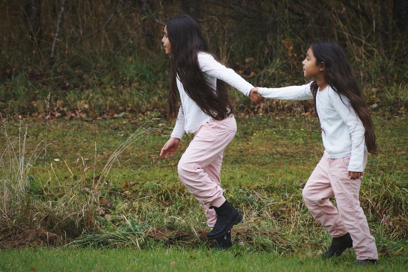 Full Length Of Sisters Walking On Grassy Field