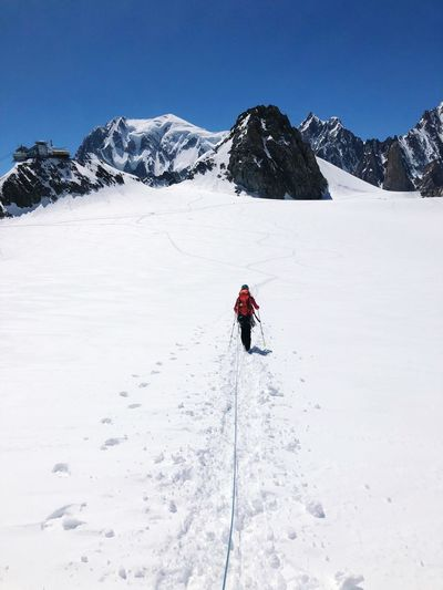 Rear view of person hiking on snowcapped mountain