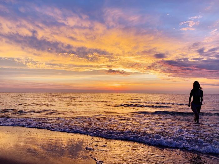 Woman wading in sea against cloudy sky during sunset