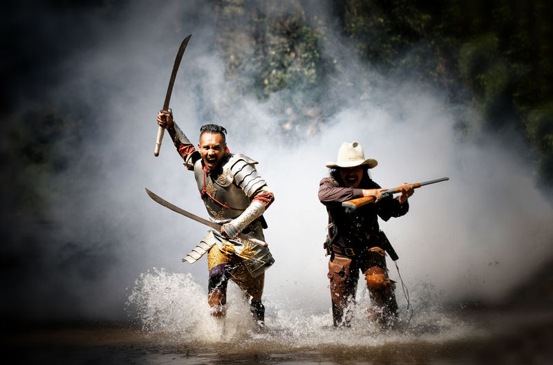 Portrait of hunters running in against smoke