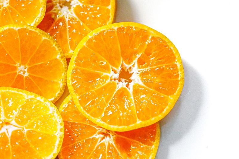High angle view of orange fruit on white background