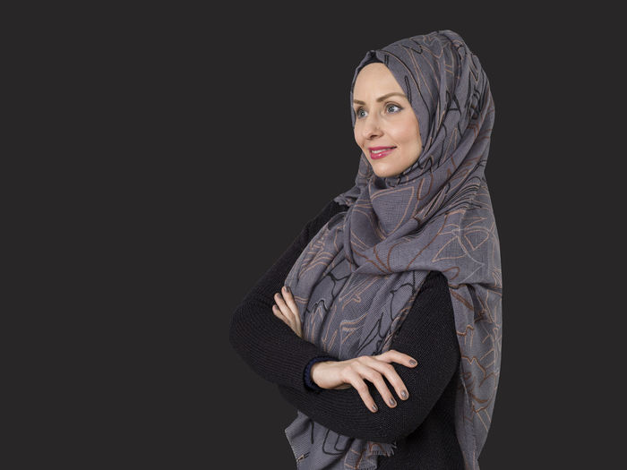 Smiling Woman Wearing Hijab While Standing Against Black Background