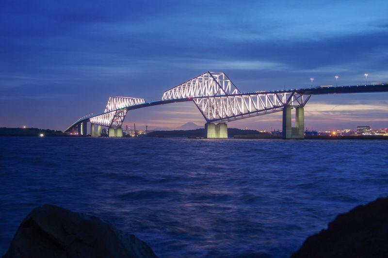 Bridge over sea against cloudy sky at night