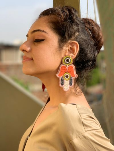 Profile view of young woman wearing earrings while standing outdoors