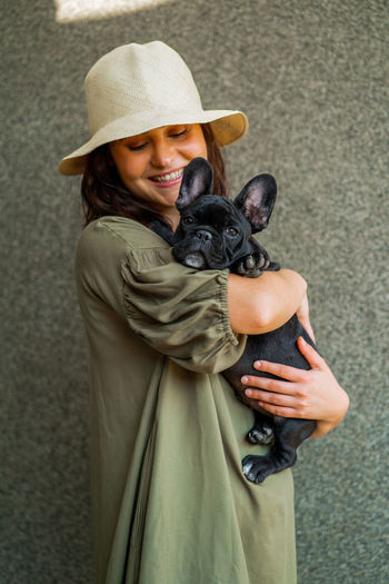 Woman holding a dog wearing hat
