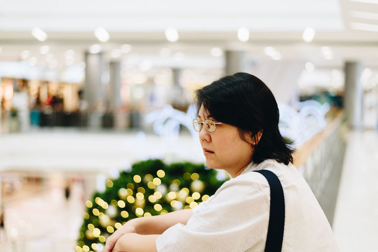 Side view of thoughtful woman looking away at shopping mall