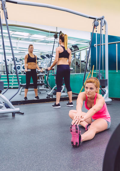 Beautiful woman stretching in a fitness center and female friend doing exercises with dumbbells in the background Athletic Exercising Females Slim Woman Activity Beauty Club Equipment Fit Fitness Gym Healthy Lifestyle Indoors  Muscles Muscular Real People Sport Streching Train Training Two People Vertical Weight Workout