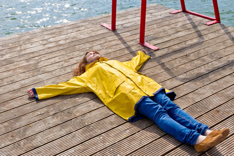 Young woman in a yellow raincoat lying on a jetty Yellow Relaxation Lying Down Lifestyles Leisure Activity Women Nature Water Outdoors Day Relaxation Relaxing Woman Girl Raincoat Nature Happy Rest Spring Psychology Teenager Enjoying Life Healthy Eating Time Jetty
