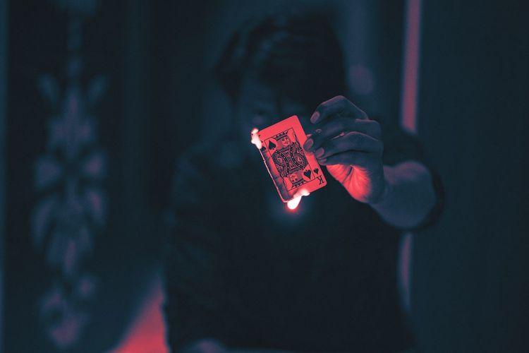 Close-up of man holding burning playing card